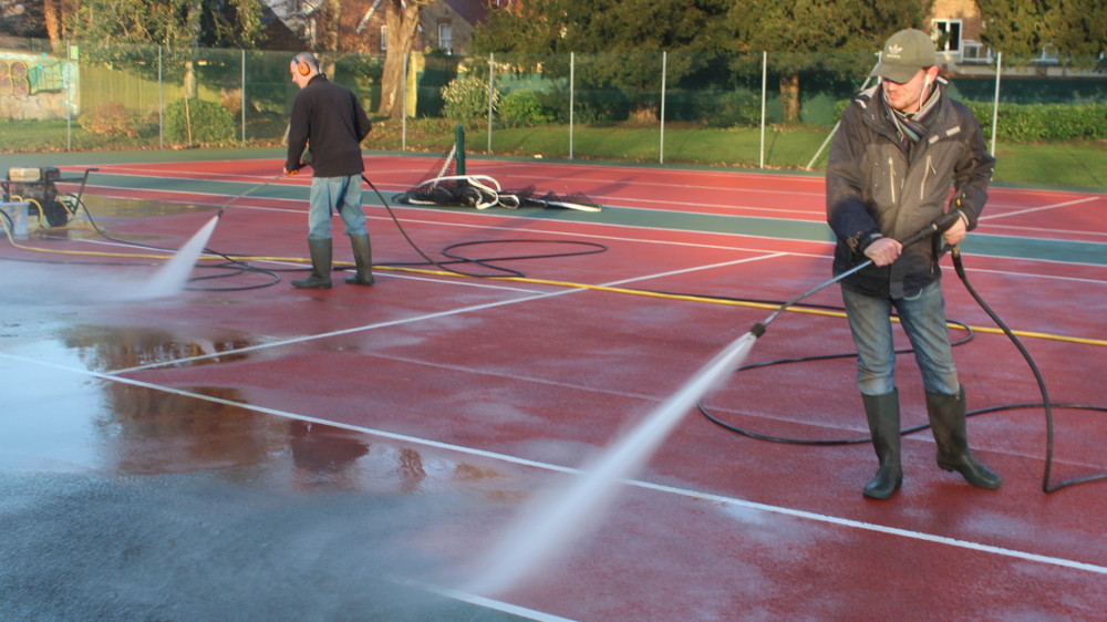 Chris (left) and Jordan from Colourcourt are high-pressure spraying courts 5 and 6.